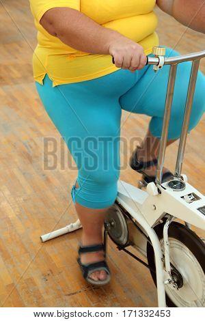 body of overweight woman exercising on bike simulator