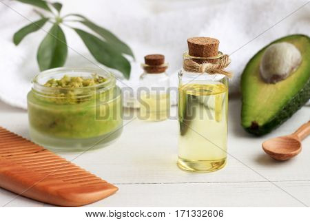 Home spa. Avocado oil facial mask, oil in bottle, white and green towels. Natural skincare treatment.