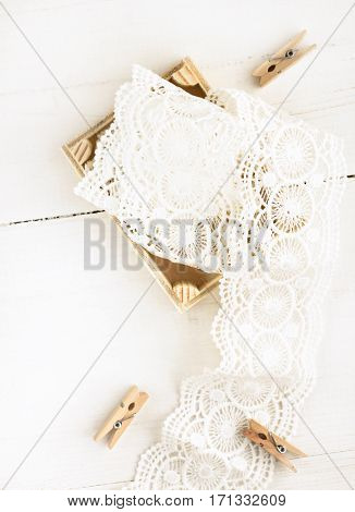 Lace ribbon textile feminine decor in wooden box, top view on bleached white table, soft light and focus.