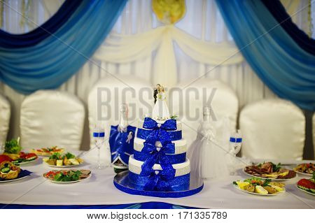 Wedding Cake With Blue Ribbons And Figurine Of Newlyweds On Table.