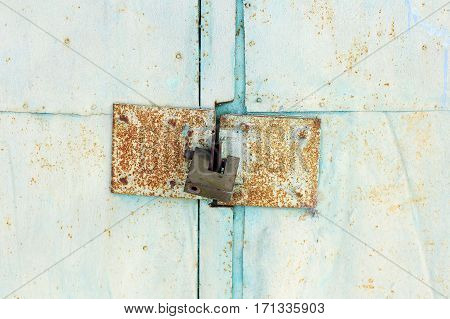 iron lock. Old iron door closed behind the lock. Green background