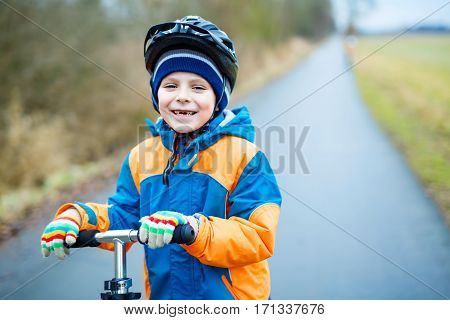 cute little school kid boy riding on scooter in park nature. children activities outdoor in winter, spring or autumn. funny happy child in colorful fashion clothes and with helmets. High speed