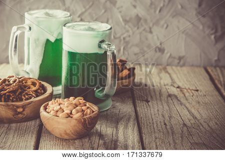 Green beer in mugs and snacks on rustic wood background, copy space