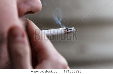 man with stubble lights a cigarette and smokes