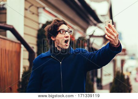 Young man taking selfie and grimacing with opened mouth