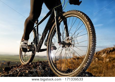 closeup feet athlete mountainbiker and wheel of a sports bicycle. Cycle in the background of blue sky with clouds. Spting season. Landscape with hill and horizon.