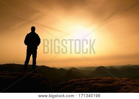 Sportsman in black with hands in pockets stand on the peak in rock empires park and watching over the misty and foggy morning valley to Sun. Silhouette of man.