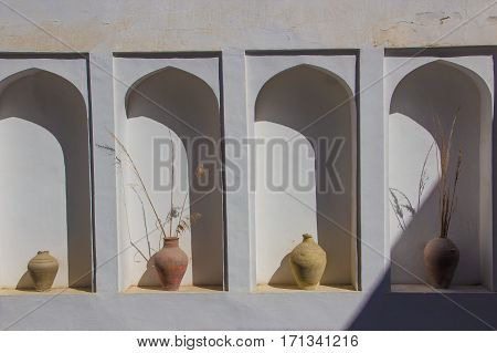 An arched niche in a white wall with old clay vases in Bukhara Uzbekistan. Old aged plastered faux arch false fake window