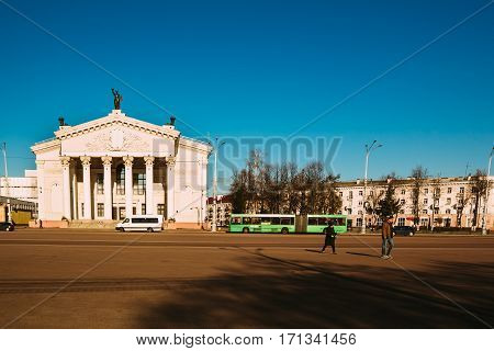 Gomel, Belarus - March 27, 2016: City transport and people walking on Lenin Square near Gomel Drama Theatre