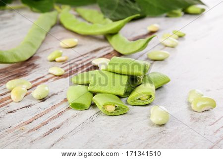 Sliced green beans on white wooden table. Healthy legume eating.