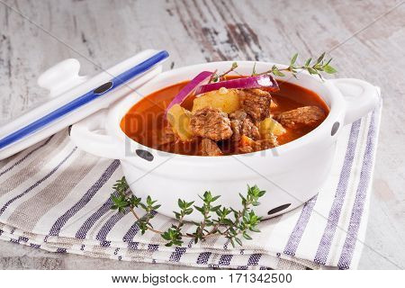 Traditional goulash in crock on white wood table. Rustic vintage style traditional dinner.