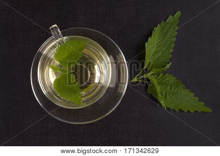 Fresh stinging nettle tea and leaves on black background top view. Alternative herbal remedy.