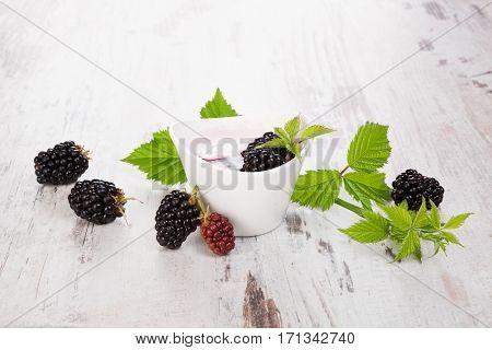 Blackberry dessert and fresh blackberries on white wooden table. Healthy fresh dessert.