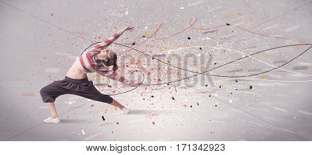 A young contemporary energetic dancer in action in front of a grey wall background with lines, spray dots and splatter concept
