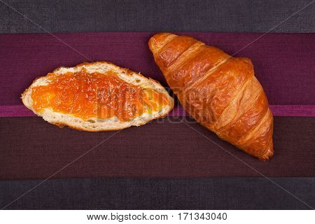 Croissants with jam on black background top view. Culinar pastry eating.