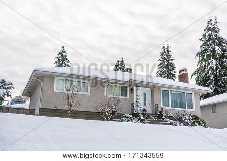 Single family residential house with front yard in snow. Average North American house on winter cloudy day