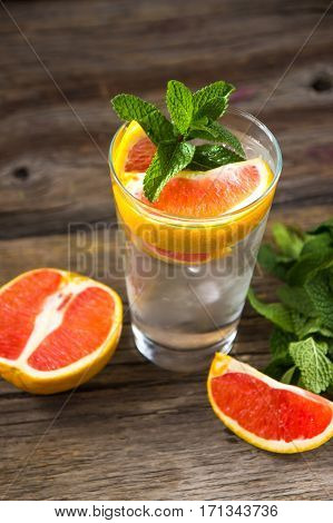 Fresh Lemonade In A Glass Beaker With Ice, Green Mint, Red Orange And Lemon On The Wooden Table