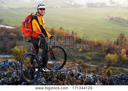 Cyclist standing on the top of a hill and watching the view. Cycler in the helmet and sunglasses with red backpack. Beautiful landscape with hill and green field. Spring season in the countryside.