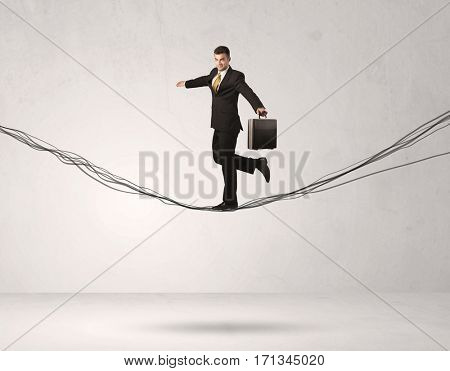 A confident businessman with briefcase walking forward on drawn lines, cables in empty grey  space concept