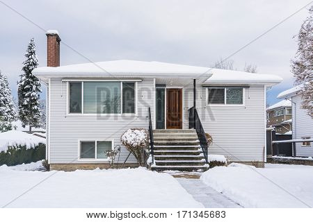 Residential house with front yard in snow. Modest North American house on winter cloudy day