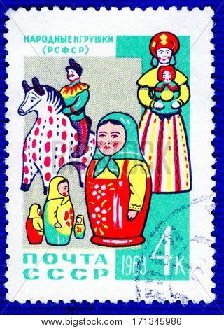 USSR - CIRCA 1963: Postage stamp printed in USSR with a picture folk toys (Russia) a matrioshka, rider and doll, from the series