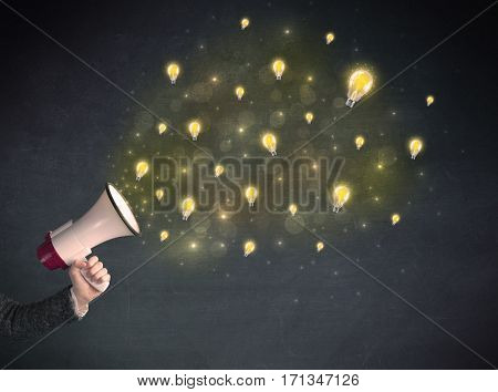 Caucasian business hand holding megaphone with yellow lightbulbs