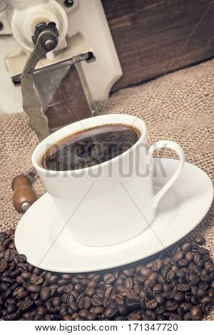 Skewed view of the vintage photo of the cup of coffee standing on the burlap sack. Around it are scattered coffee beans. The part of manual coffee grinder is standing in the background.