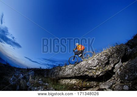 Cyclist Riding the Bike Down Hill on the Mountain Rocky Trail at Sunset. Extreme Sports. Countryside. Spring season. Cyclist in the helmet, sunglasses and with red backpack. Fisheye.