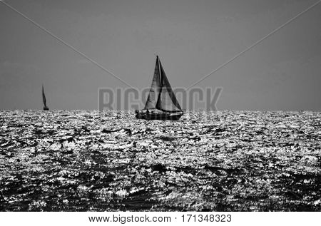 A sailboat sailing across the sea; The one in the background is doing the same.
