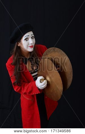 young brunette woman in a suit holding a musical mime plates (percussion instrument)