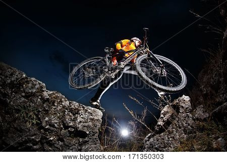 Cyclist Riding the Bike Down Hill on the Mountain Rocky Trail at Sunset. Extreme Sports. Countryside. Spring season. Cyclist in the helmet, sunglasses and with red backpack.