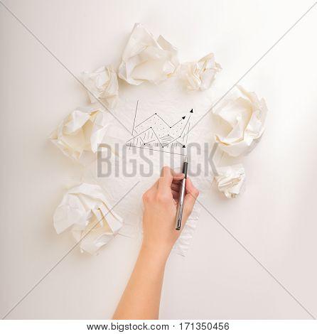 Female hand next to a few crumpled paper balls drawing a progress chart