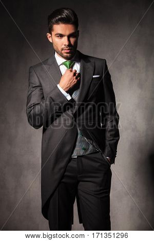 young elegant man adjusting his green tie while looking away to side in studio