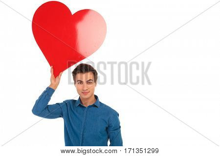young casual man holding big red heart in the air above his head on white background