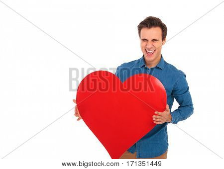 super excited young casual man laughing and holding a big red heart on white background