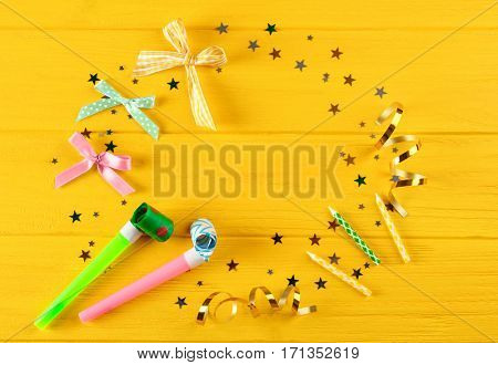 Bright confetti and festive fife on wooden yellow background