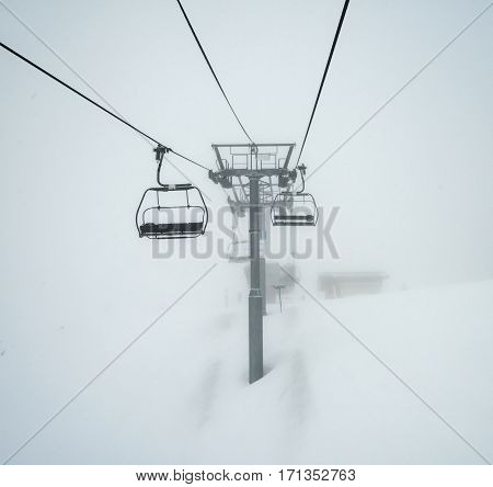 Ski Chairlift Going Over A Mountain In Fog