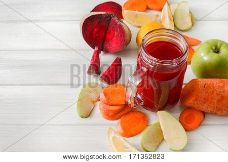 Detox cleanse drink, vegetable smoothie ingredients. Natural, organic healthy juice in glass jar for weight loss diet or fasting day. Beetroot, apple, carrot and lemon mix on white wood, copy space