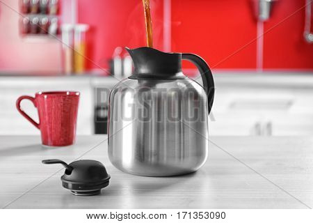 Pouring coffee into thermos kettle on kitchen counter