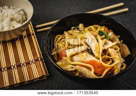 Asian or chinese noodles with chicken noodles and vegetables