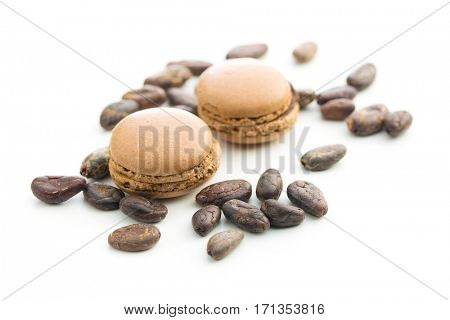 Sweet chocolate macarons and cocoa beans.