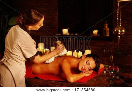 Masseur do massage of woman in spa salon. Girl on candles background in massage spa salon. Luxary interior in oriental therapy salon. Close up of female massage hands give herbs hot ball therapy.