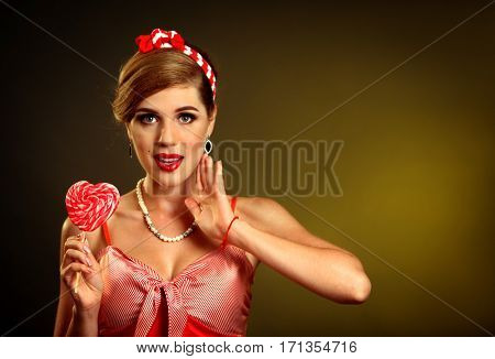 Woman eating lollipops. Girl in pin-up style hold striped candy. Pin up retro female style. Female wearing red dress.