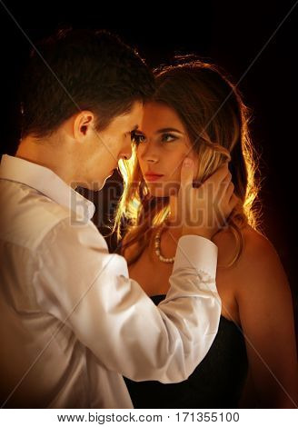 Couple kissing indoor. People in love dancing together. Portrait of sexy romantic man and woman in luxury evening interior .