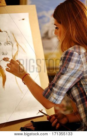 Artist painting on easel in studio. Girl paints portrait of woman with brush. Female draws self-portrait. Indoor home interior for handmade crafts.