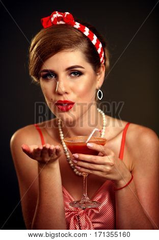 Kiss blow of pin up girl drink bloody Mary cocktail . Pin-up retro female style. Girl pin-up style wearing red dress and wind blowing.