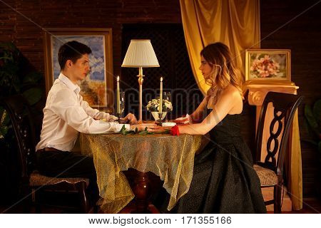 Romantic dinner for couple. Restaurant interior with candlelight for romantic date. loving couple. Happy people in love. A lot of pictures in room.