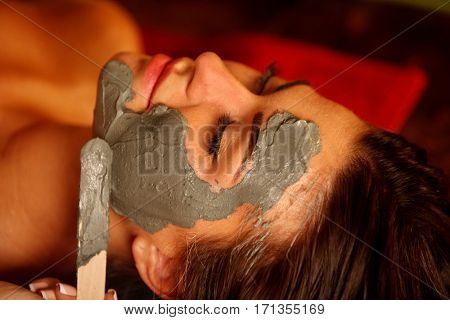 Mud facial mask of woman in spa salon. Back massage with clay full face . Girl on Luxary interior with oriental therapy room. Top view of female with flower lying on wooden spa bed.