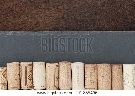 An ensemble of wine corks stone plate and cow skin resembling a flag