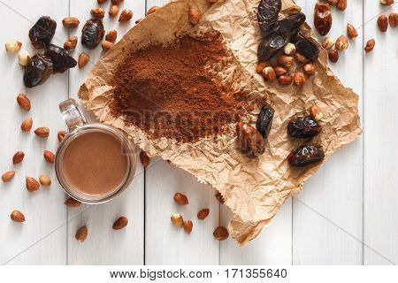 Detox cleanse drink background. Chocolate smoothie ingredients. Natural healthy juice in glass jar for diet or fasting day. Cocoa powder, nuts, date fruit mix on white wood, top view